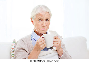 sick senior woman drinking hot tea at home