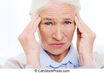 face of senior woman suffering from headache - health care,...