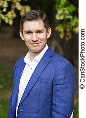 Young business man in a blue suit and white shirt on the...