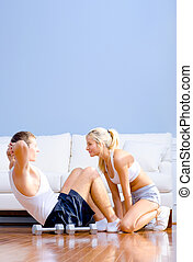 Couple Exercising on Living Room Floor - Young man performs...