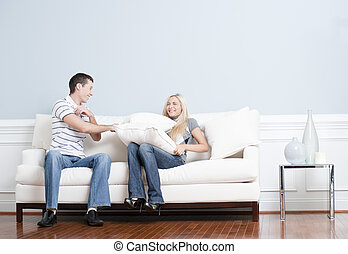 Young Couple Having a Pillow Fight on Sofa - Young man...