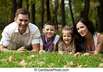 Happy family lying down in the garden
