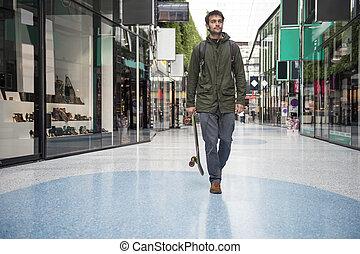 Man, stroll - Man, holding a skateboard, strolling casually...