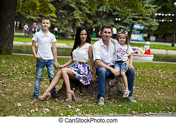 Young happy family portrait on background of the autumn park