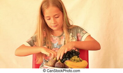 Cute girl eating grape