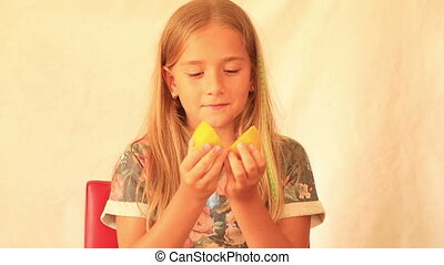 Cute girl eating lemon