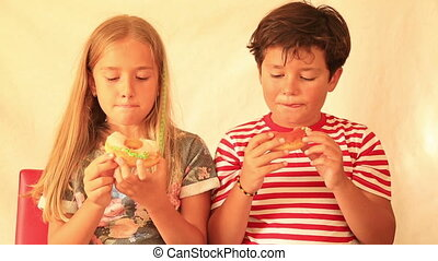 Cute little boy and girl likes donut