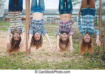 Four young funny teenage girls hanging upside down having fun