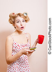 Surprized sexi pinup lady in curlers with cup and mobile -...
