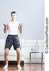 Man Using Resistance Bands in Living Room - Man standing and...
