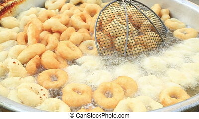 Donuts fried in big pan