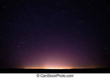 Colorful Night Starry Sky Above The Yellow City Lights Night...