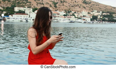 smiling girl taking picture with smartphone camera outdoors