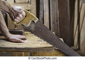 Carpenter sawing a board with a hand wood saw