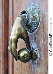 door knocker hand - door knocker shaped golden hand holding...
