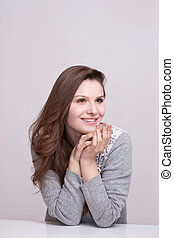 Close up portrait of a happy smiling woman resting her chin...