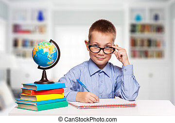 Cute schoolboy is writting isolated on a white background -...