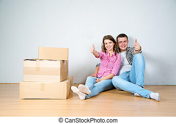 Happy young couple unpacking or packing boxes and moving...