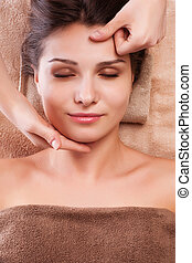 eautiful young relaxed woman enjoy receiving face massage at...