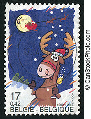 postmark - BELGIUM - CIRCA 1999: The cheerful reindeer eats...