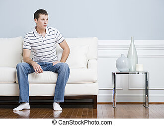 Man Sitting on Living Room Couch - Man in casual clothing...