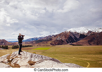 photographer standing and take a photo on rock cliff at castle hill south island new zealand beautiful and important traveling destination