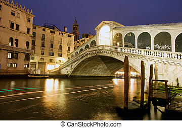 Rialto bridge, Venice - Night traffic on Grand Canal under...