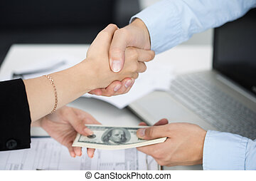 Woman and man handshake close up with the money in the other...