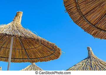 Parasol on the beach in a sunny summer day over a blue sky background