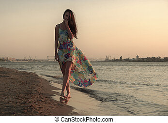 Young woman in a colorful dress on the ocean coast a lot of...
