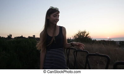 Young woman walking on sunset