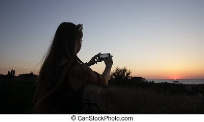 girl taking a picture with phone at sunset hd
