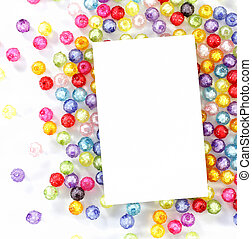 empty white paper on colorful beads on white background