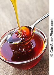 Honey dripping onto spoon - Thick golden honey drizzling...