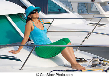beautiful woman aboard a yacht sunbathing with sunglasses