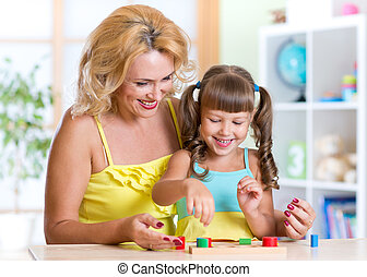 kid and mother playing together with educational toy
