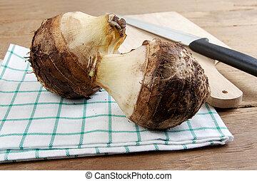 taro - Head two taro on white cotton and wood table