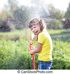 Cheerful kid watering plants from hose spray in garden at...