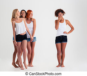 Afro american women standing while friends laughing with her...
