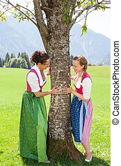 Two bavarian women cling to a tree and smile at each other -...
