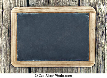 Empty vintage blackboard with wooden frame on a wooden...