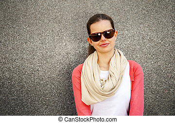 happy young woman is smiling with a blank wall outside with glasses