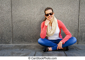 happy young woman is smiling with a blank wall outside with sunglasses