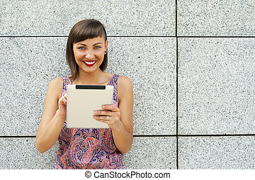 Young modern woman using tablet in the city by the wall,...
