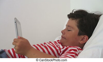 Young boy gaming on tablet computer