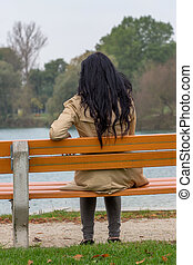 young woman thoughtful - a young woman sitting pensively on...