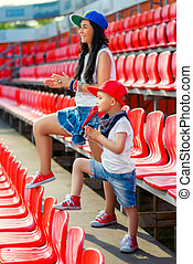 Rapper attitude rap singer hip Hop Dancer performing. Stylish woman and little boy sitting in the stands of stadium