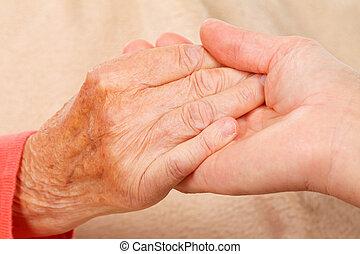 Togetherness - Caregiver holding elderly patients hand at...
