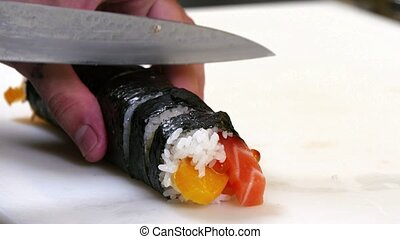 Sushi Chef Cutting Salmon Roll - A sushiman cuts salmon,...