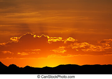 Desert sunset with glowing red sky, Namibia, southern Africa...